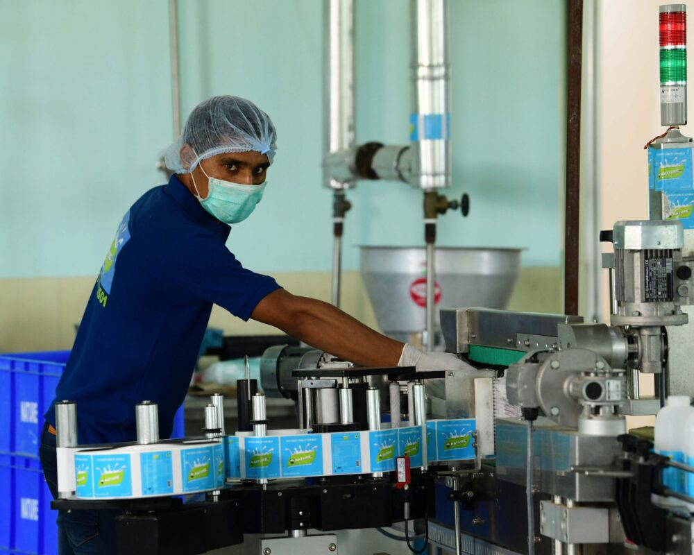 Worker handling Milk cane packaging and labeling process in factory